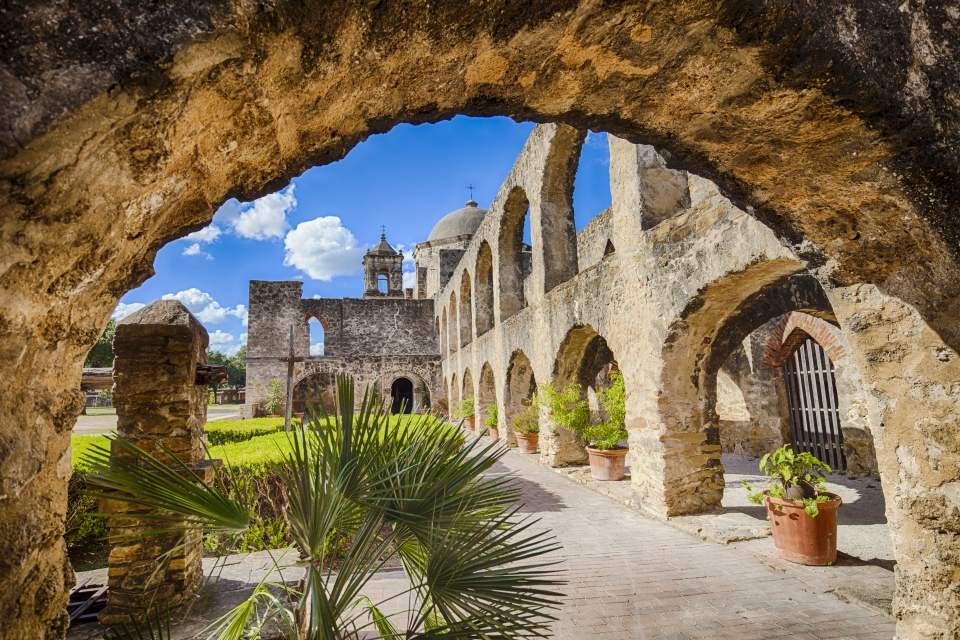 View through one of the arches to the rest of the stone arched building at Mission San José at San Antonio Missions National Historical Park