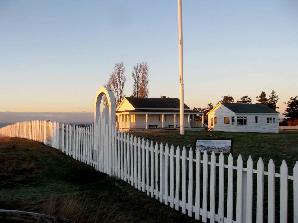 white picket fence with 2 white buildings in the background at American Camp at San Juan Islands National Historical Park