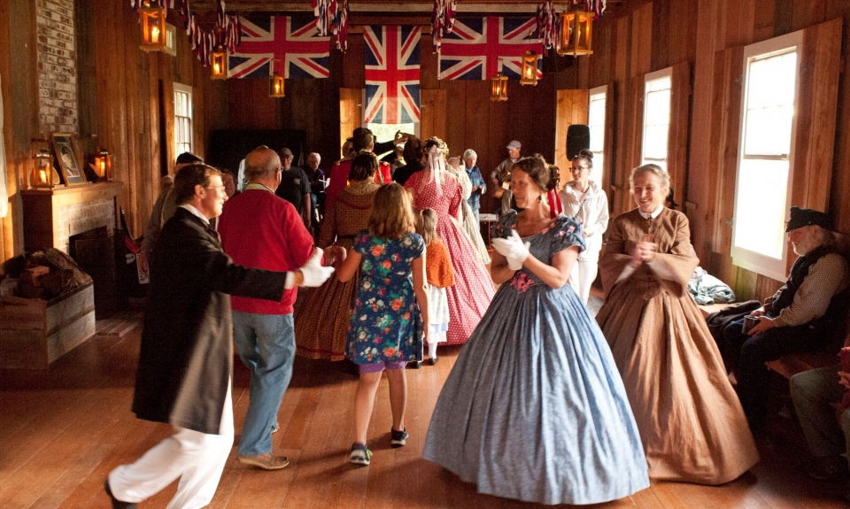 People dressed in colonial ball attire dancing in a building with Union Jack flag hanging from the ceiling at San Juan Island National Historical Park