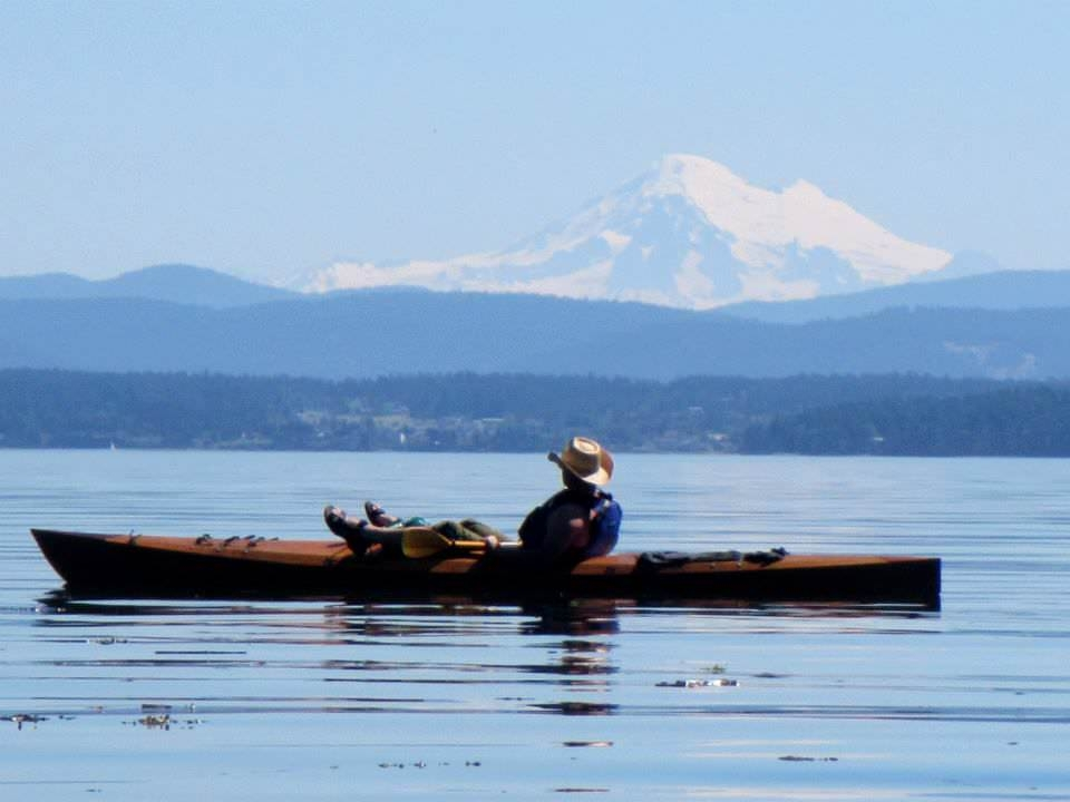 Kayaker resting on the water with a snow-capped mountain in the background at San Juan Islands National Historical Park