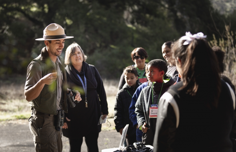 A park ranger gives a demonstration to a group of teachers and students