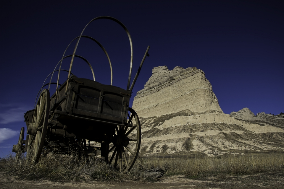 Uncovered covered wagon in the dessert with Scott's Bluff National Monument in the background.