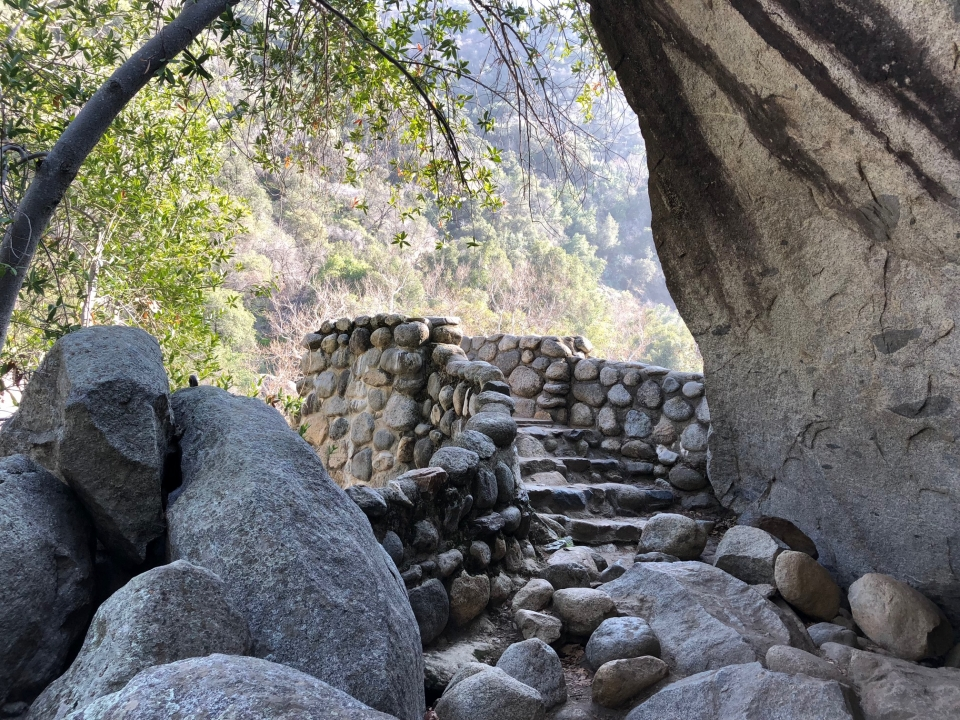 Stone stairs surrounded by boulders leading up to a balcony with a view of the foothills