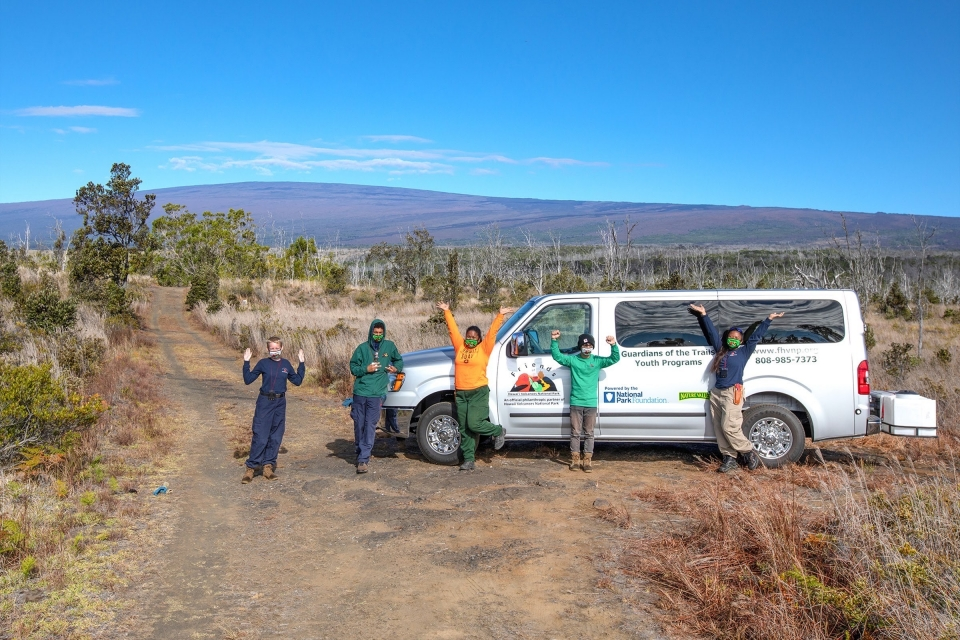Five service corps members posing along side a white van in Hawai'i Volcanoes National Park