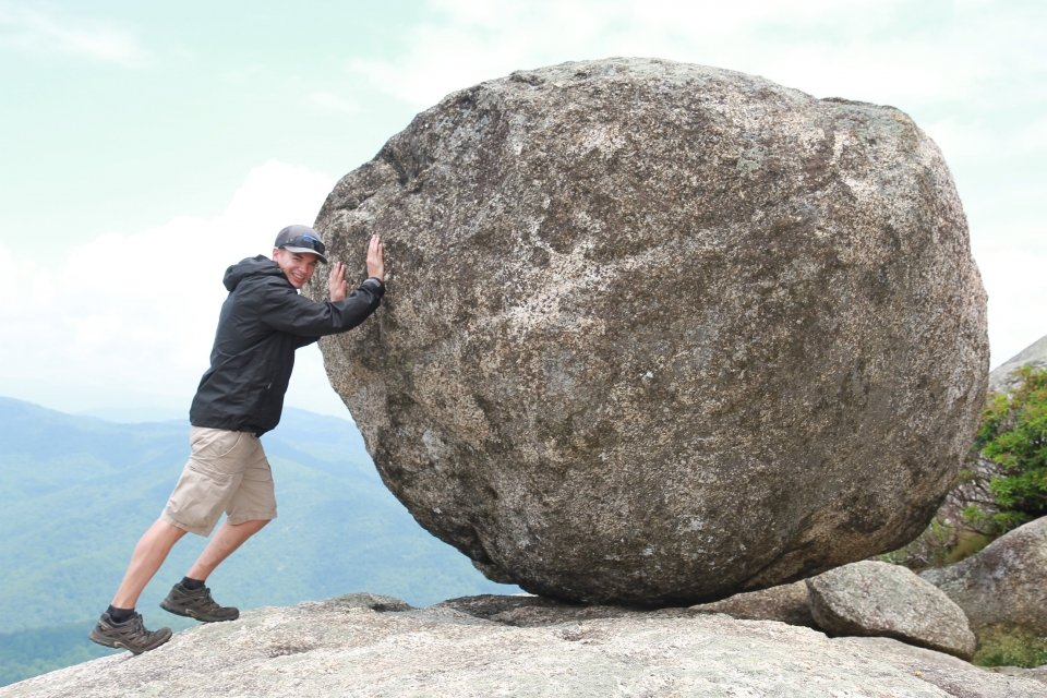 Man pretending to push a giant boulder bigger than he is at Old Rag hike in Shenandoah National Park