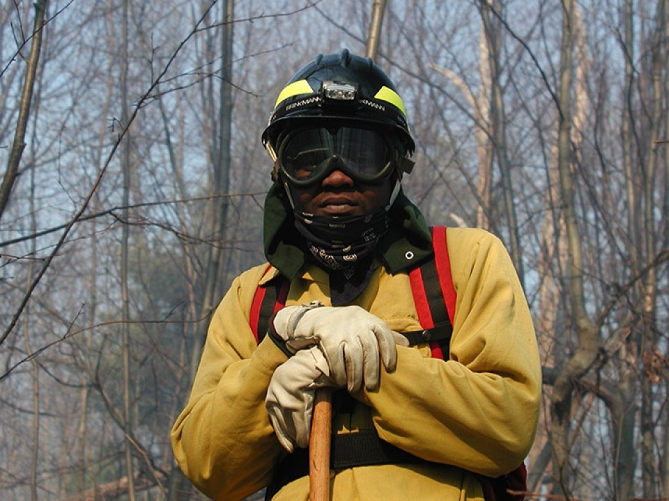 A National Park Service employee in firefighting gear poses for the camera