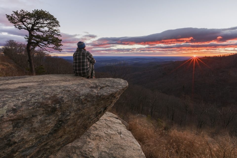 a visitor watches the sun rise on a high overlook