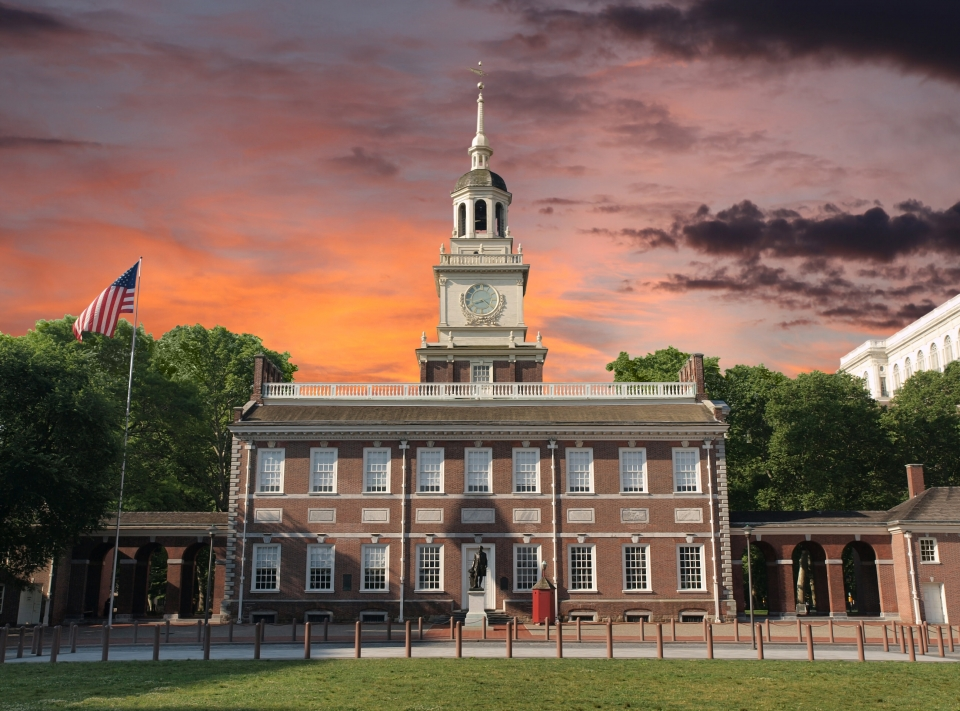 The red brick, symmetrical, Georgian-style Independence Hall illuminated by the reds and oranges of a sunset sky.