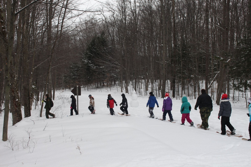 A group of 4th graders snowshoeing through the snowy forest of Sleeping Bear Dunes National Lakeshore