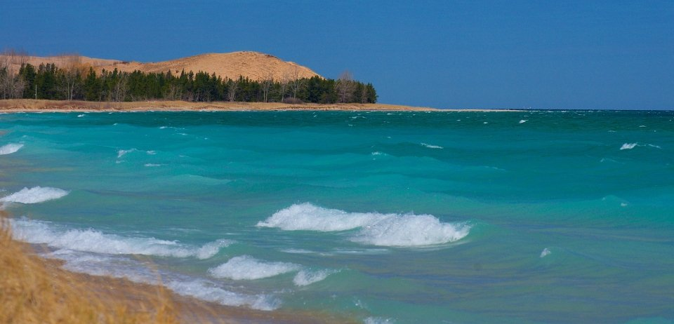 Bright blue waters along a warm brown shoreline. In the background, a large dune crests over the water