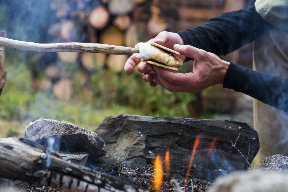 A hand reaches out to grab a toasted marshmallow off a stick, hovering over a fire, to make s'mores with chocolate and graham crackers