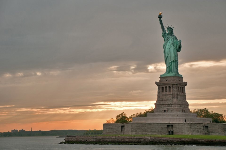 Statue of Liberty National Monument against an orange sunset