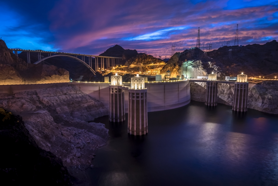 Illuminated structure of the Hoover Dam under a blue and pink-cloud evening sky.