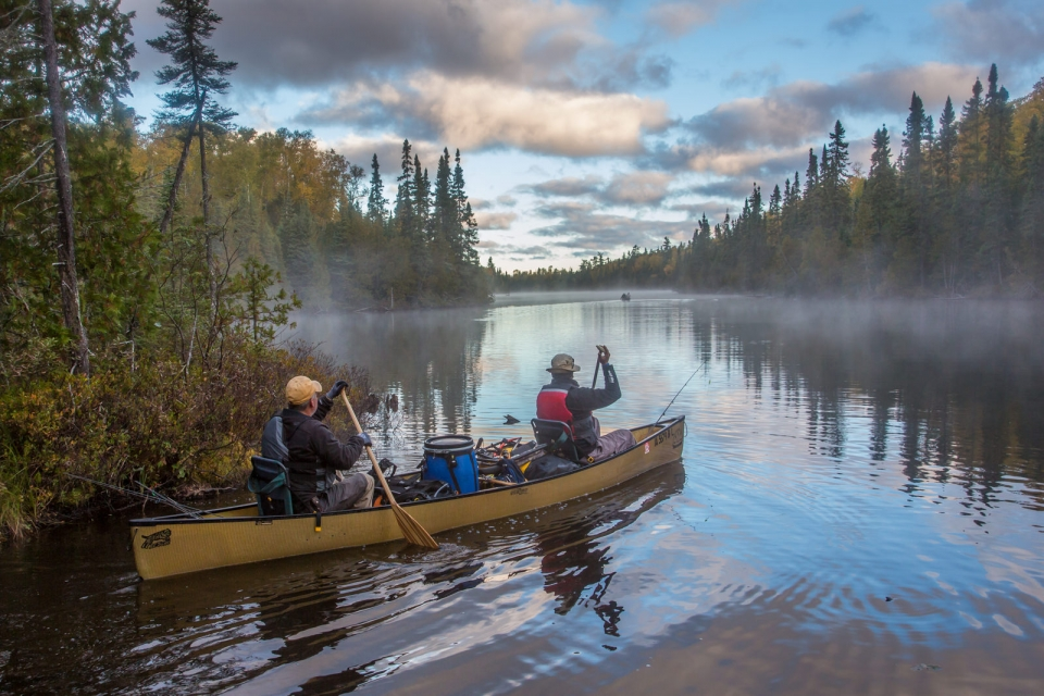 Two men canoeing down a peaceful, foggy river, with evergreen trees lining the banks at Superior National Forest