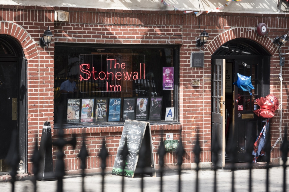 Neon sign of Stonewall Inn in the window on a brick building