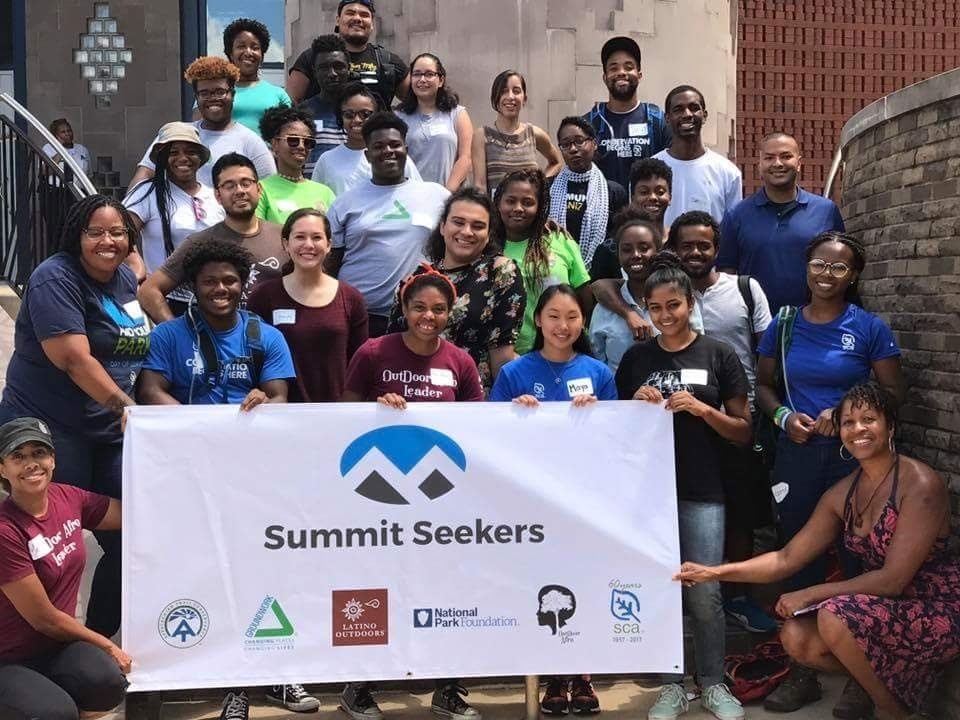 A diverse group of youth standing behind a Summit Seekers banner