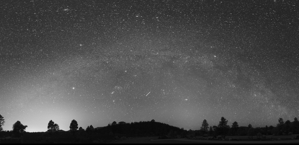 Black and white image of the Milky Way over Sunset Crater Volcano National Monument, a national park in Arizona