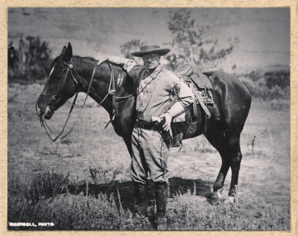 Black and white photo of Theodore Roosevelt standing next to his horse