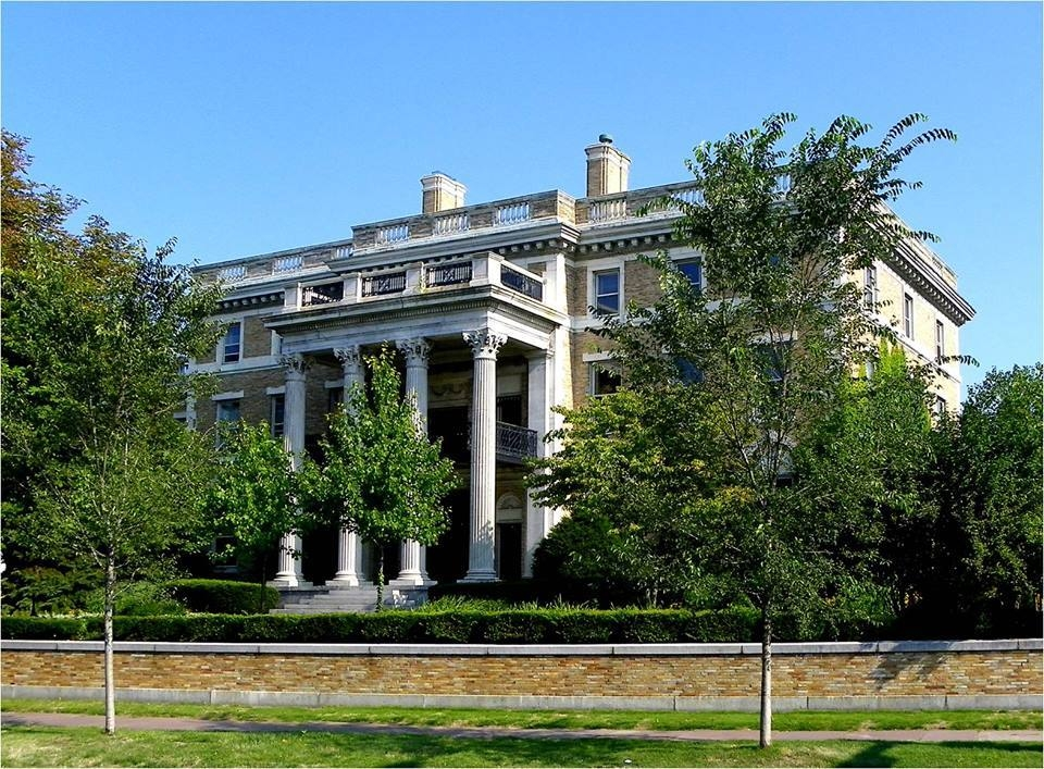 Stately manor with large columns framing the facade and entrance. Outside, tall trees reach three stories into the sky