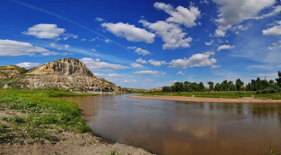 The muddy Little Missouri River under blue skies at Theodore Roosevelt National Park