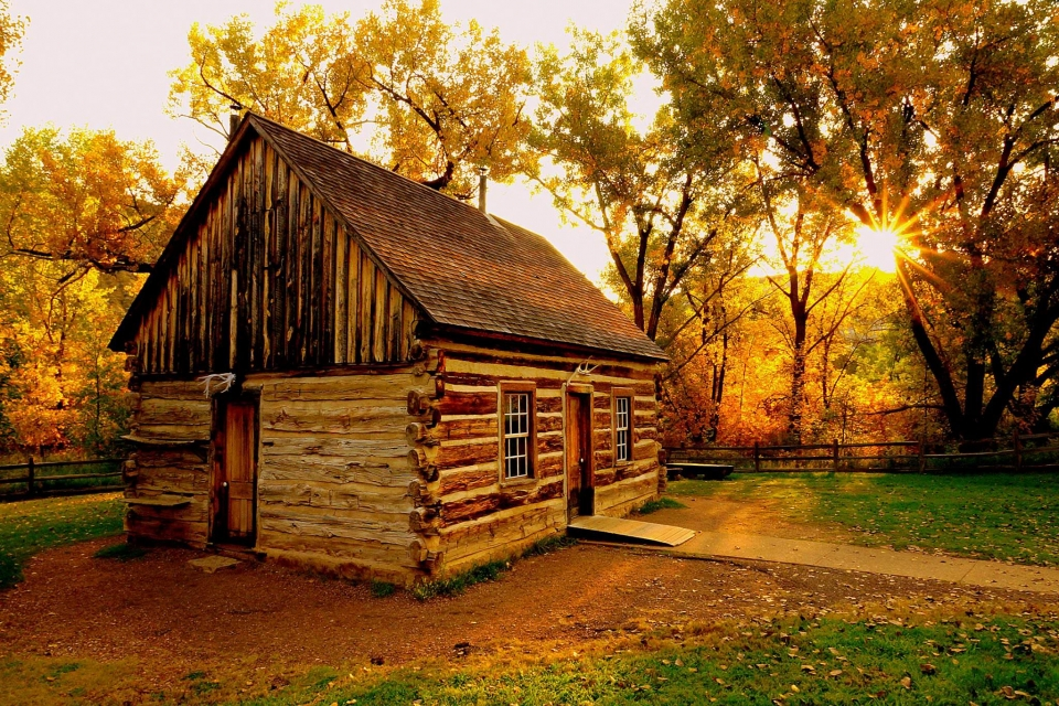 Golden sun low in the horizon through trees behind a wooden Maltese Cross Cabin at Theodore Roosevelt National Park