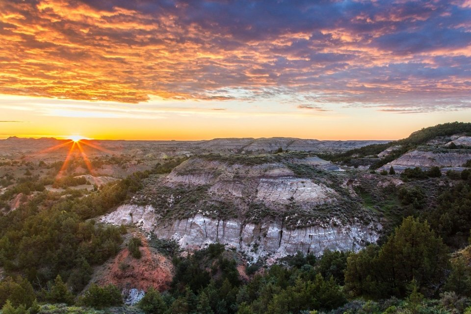 A golden sunset over the rolling bluffs of the badlands at Theodore Roosevelt National Park