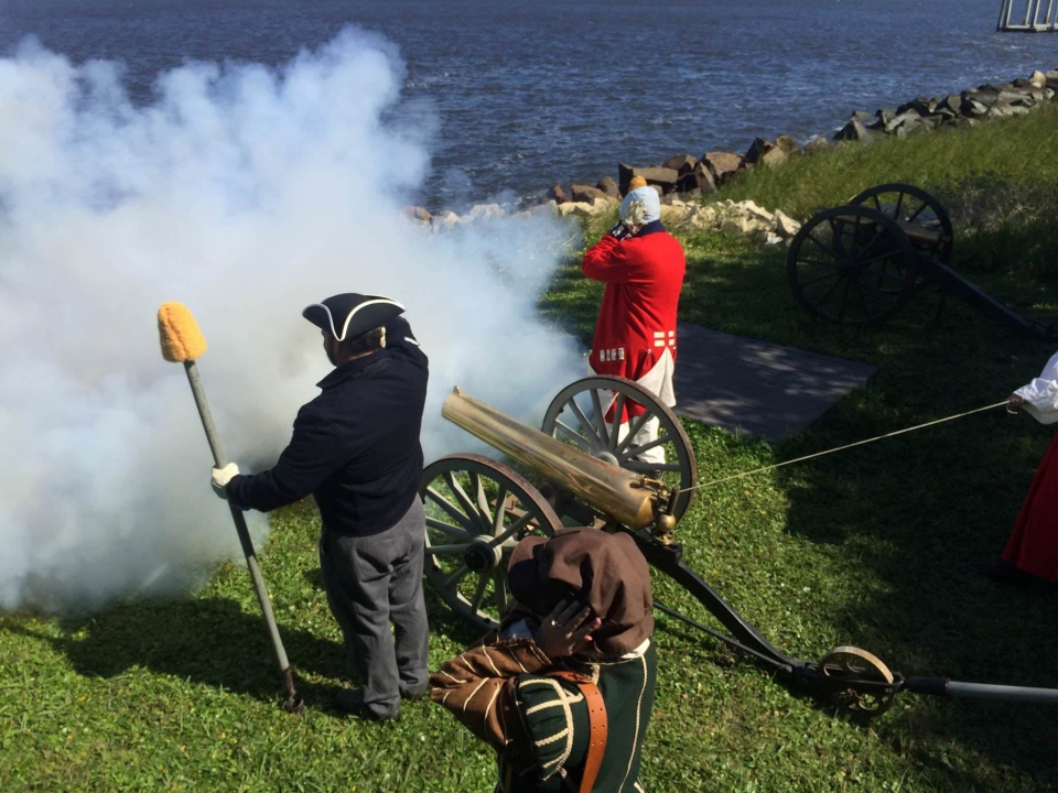 Living history rangers fire a canon at Fort Caroline National Monument