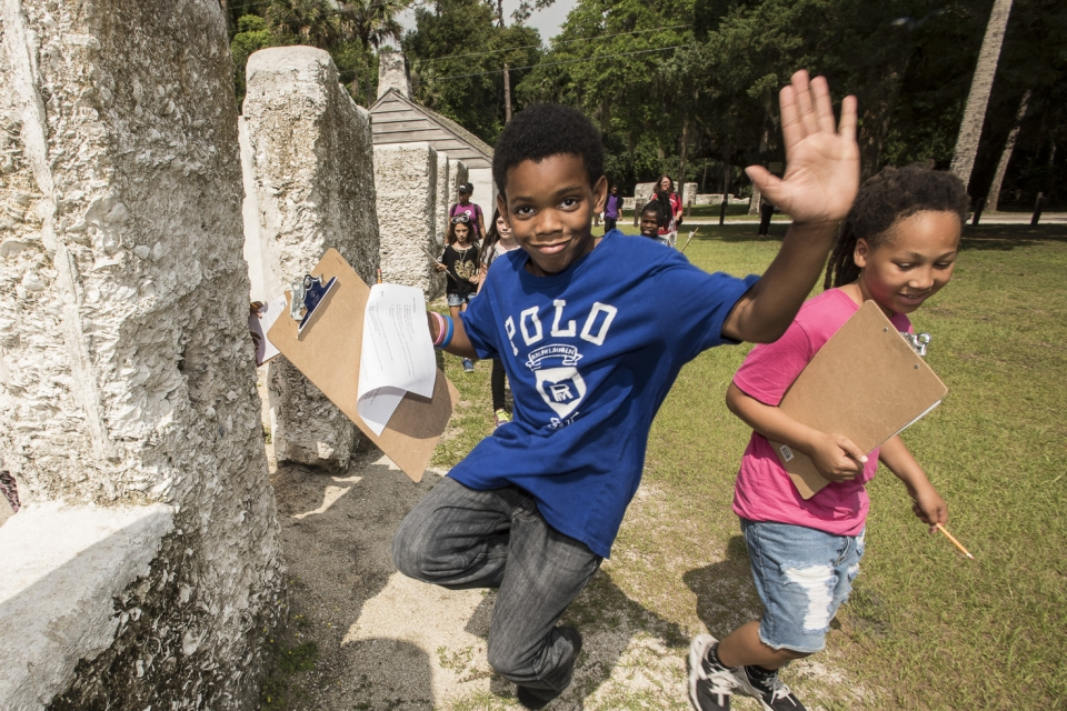 child jumping on a field trip to Timucuan Ecological and Historical Park