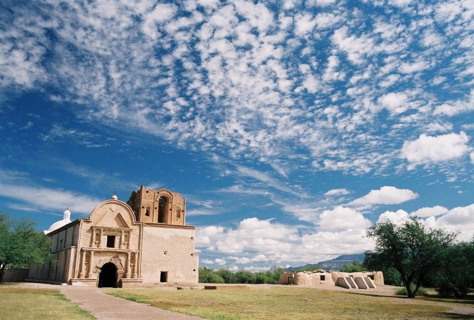 mission church and grounds with interesting cloud pattern in very blue sky