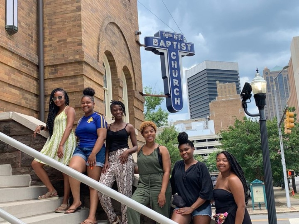 A group of young women stand on the steps of 16th Street Baptist Church
