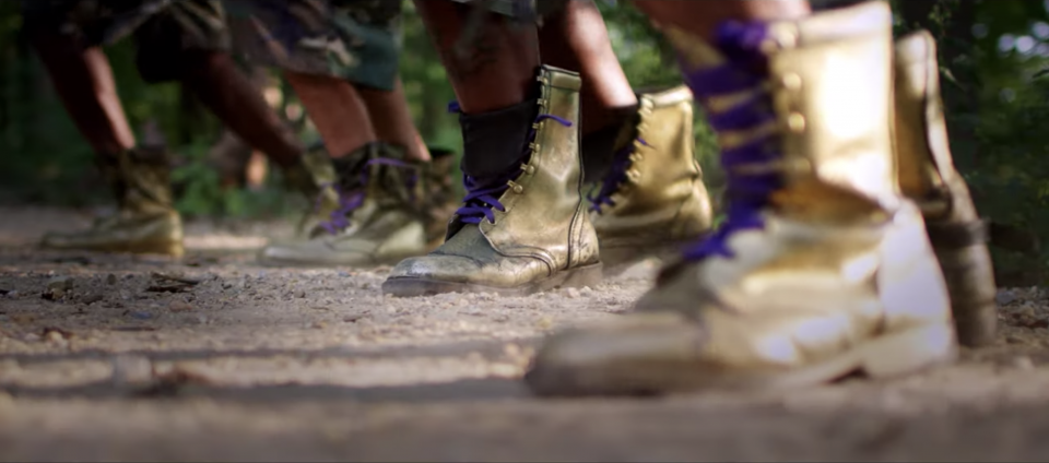 A row of gilded combat boots stomp on a dirt ground
