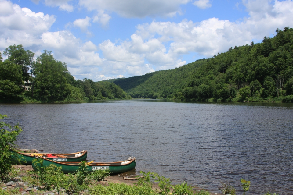 Two green park ranger canoes on the shore at Upper Delaware Scenic and Recreational River