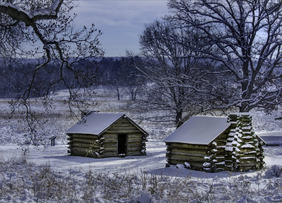 a layer of snow rests upon log cabins and rolling fields at Valley Forge National Historical Park