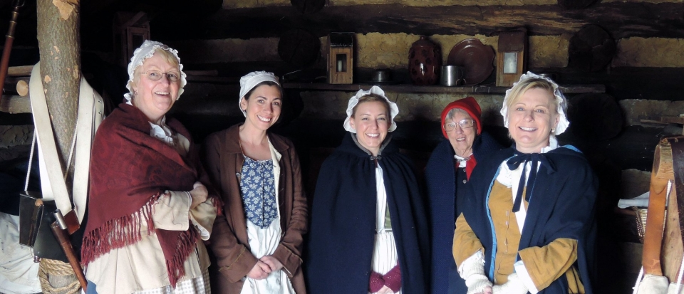 Five women in colonial era clothing standing in a log cabin at Valley Forge National Historical Park