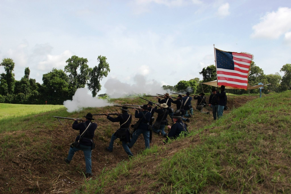A group of union soldiers firing muskets on a grassy hill with the Union Flag waving in the breeze at Vicksburg National Military Park