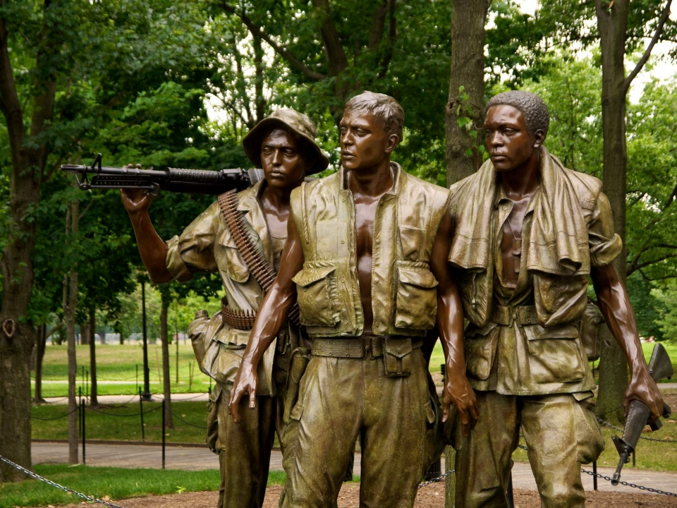 A statue of three Vietnam War soldiers gazing toward the Memorial Wall.