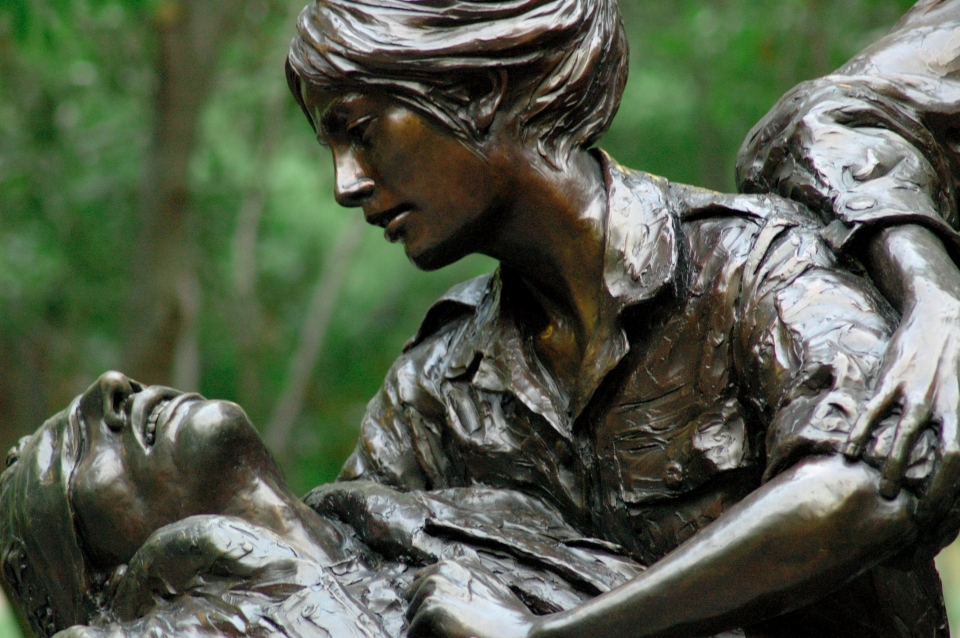 Close up a bronze statue in which a woman cradles a fallen soldier