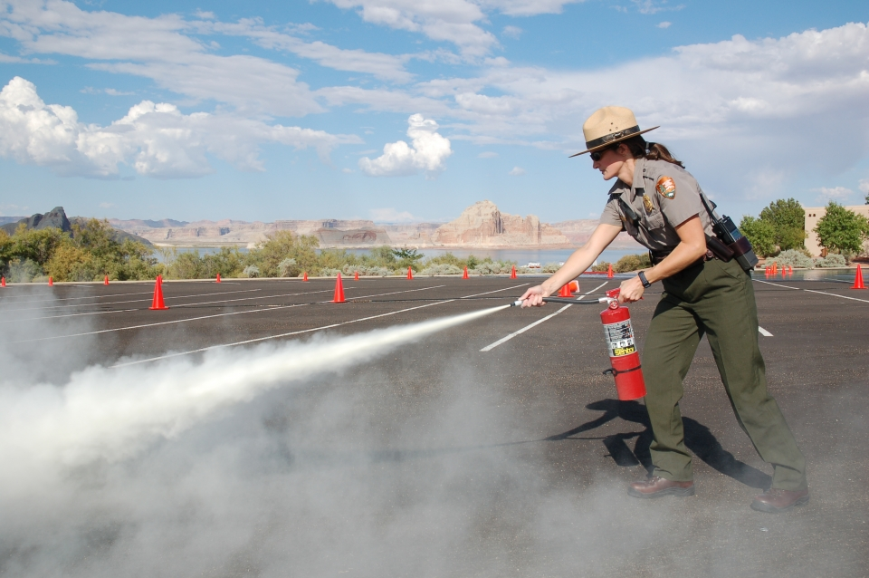 A woman in a National Park Service uniform holds and activates a fire extinguisher.