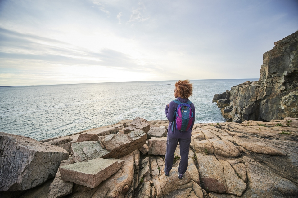 A woman stands on a rocks overlooking water. She is wearing a rain proof athletic jacket and a backpack.