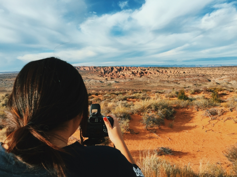 Back of a woman's head with a camera in front of her in front of a red dessert