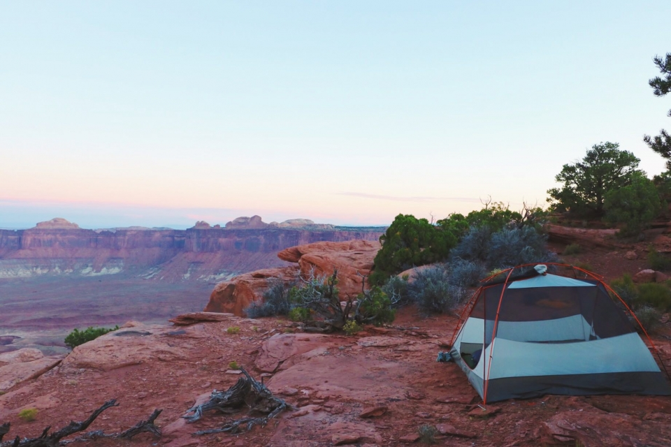 Open tent in the corner with the red sandstone valley of Canyonlands National Park behind