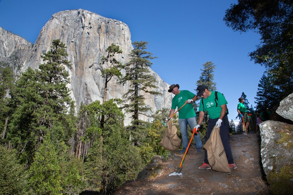 Volunteers in green shirts clean up a trail in Yosemite National Park