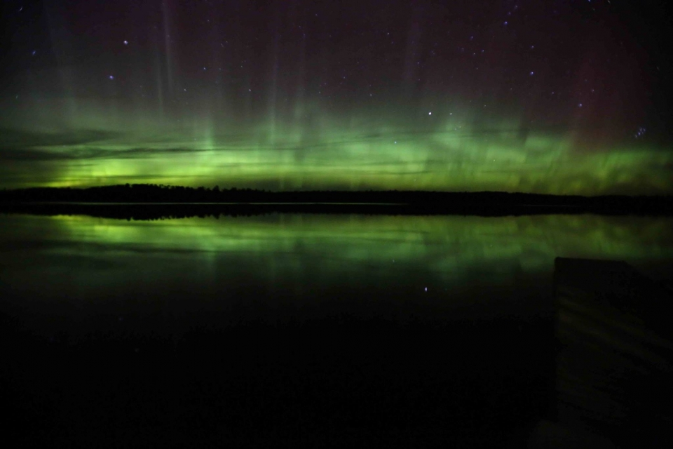 the green lights of the aurora borealis over the water at Voyageurs National Park