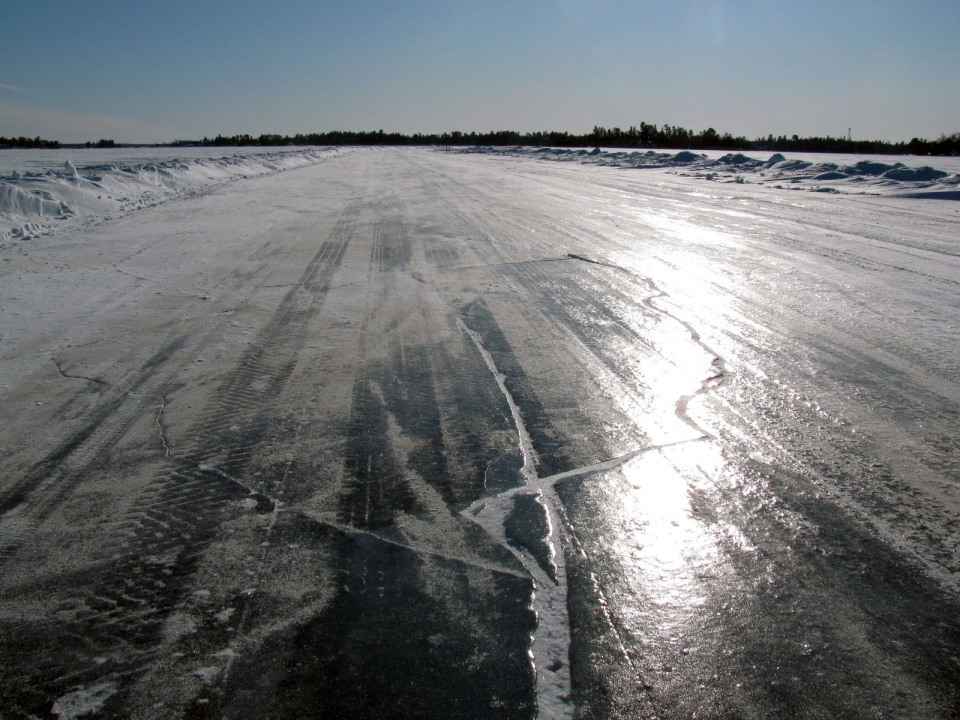 Sunlight gleams across an expanse of ice, streaked with tire tracks and lightly dusted in snow