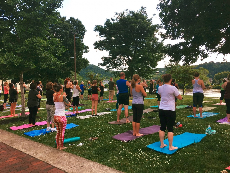 A crowd of people standing on yoga mats on the grass at Wheeling National Heritage Area