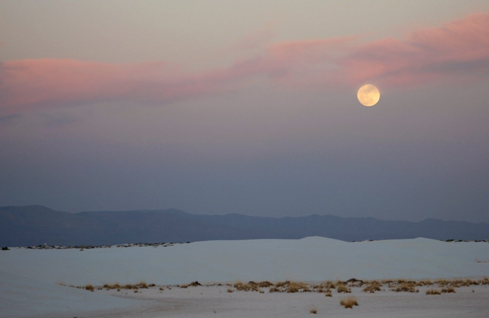 The moon stands alone with pink-hued clouds over White Sands National Monument.