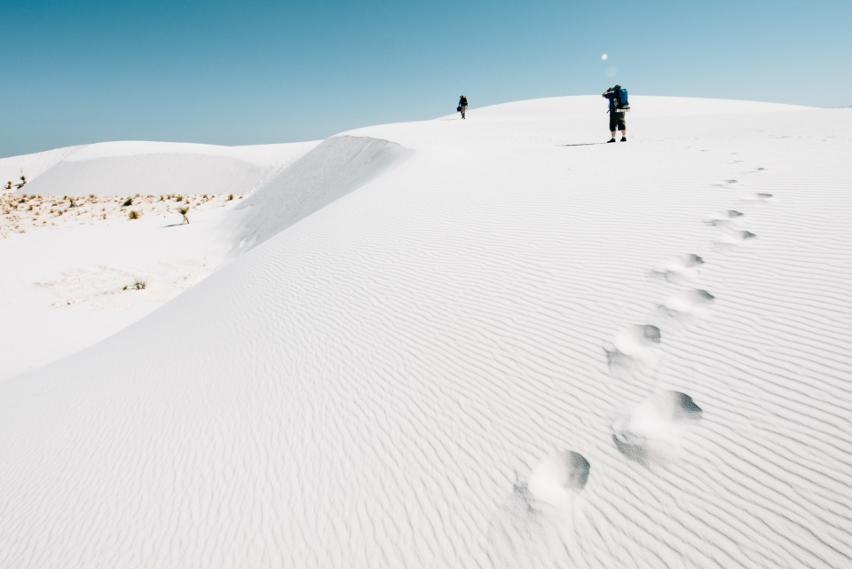 People hiking in the white sand dunes of White Sands National Monument