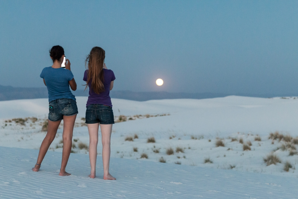 Two girls taking a photograph of the rising full moon at White Sands National Park