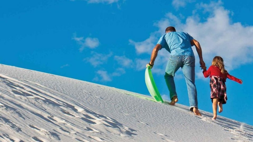 A man walking up white sand dunes with his daughter and a sled in White Sands National Monument