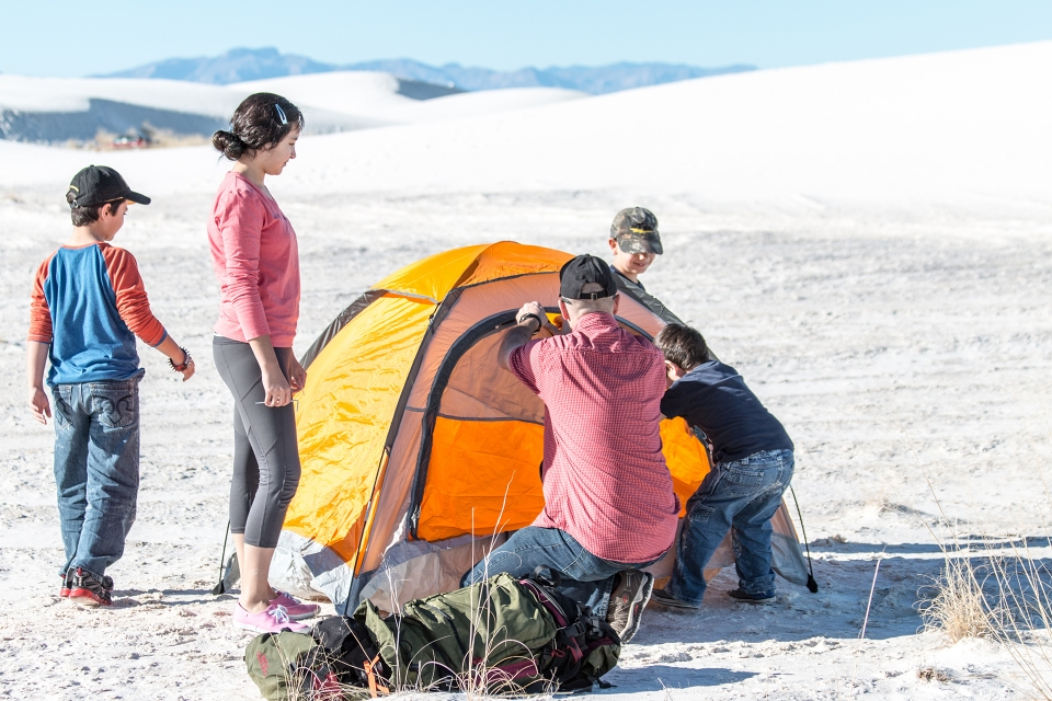 A family sets up their tent at a back country site